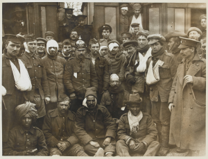 British and Indian wounded at Neuve Chapelle, on the way to the hospital base, 1915. One of the British is wearing a German helmet. Shows a group of wounded Germans, British and Indians next to a hospital train. (National Army Museum)